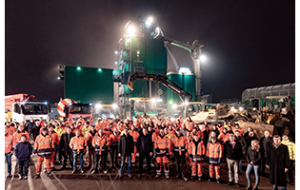 Das Team von AMW Stamer. Im Hintergrund Teile des Maschinenparks und das Asphaltmischwerk.
